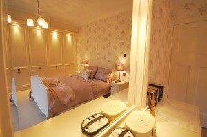 Bright cream and dusk pink fitted bedroom furniture.