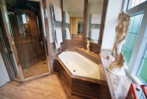 Brown marble bathroom with panels - white diamond shaped bath and walk in shower.