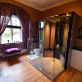 Bathroom with centre placed shower and arched window with purple curtains