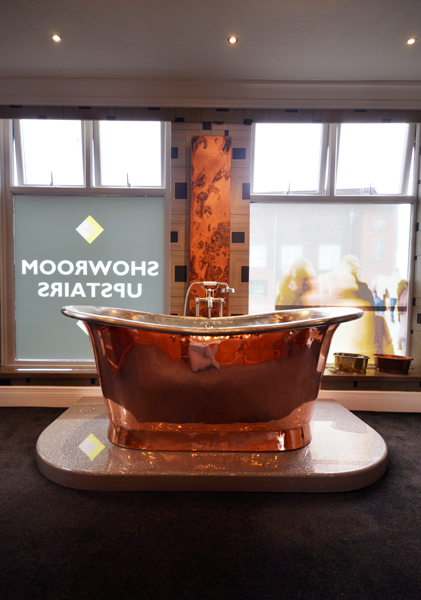 Copper bath with roll top in designer bathroom showroom in Manchester