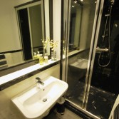 Black and white style bathroom with large shower, white sink and worktop