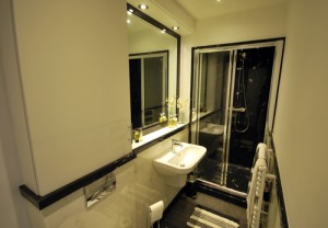 Bl;ack and white bathroom with large black shower and black shower tray, vanity top and white cabinet.