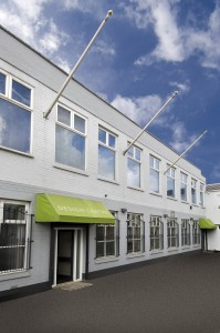 Langley Interiors furniture showroom with greay building and lime green covers.