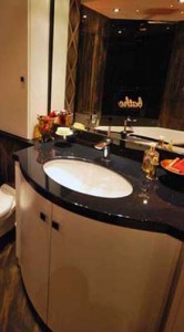 White curved bathroom cabinet with black sparkle vanity top with white ceramic basin.