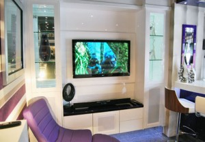 TV furniture with TV, display area with lighting, glass shelves in white high gloss with purple accessories.