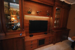 Real wood storage unit with wall hung TV, lit glass cabinets and shelving