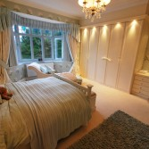 Cream bedroom furniture with spotlights.