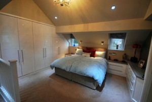 White high gloss bedroom with sloping ceiling.