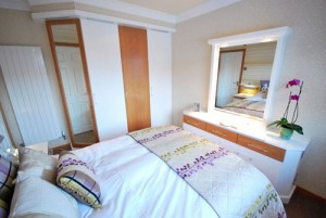 Oak and white bedroom furniture with a mirror and wardrobes.