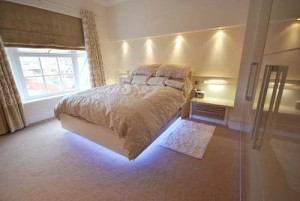 Cream high gloss fitted bedroom with lighting.