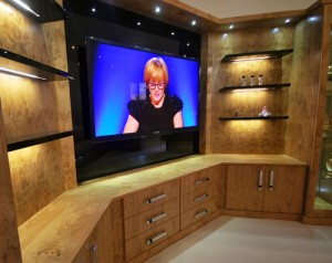 Media wall with wall hung TV, floating shelves with LED lighting, display canibets, drawers and cupboards in warm oak wood finish.