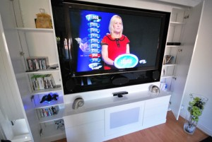 Whote high gloss lounge furntiure with games console storage and flat screen TV.