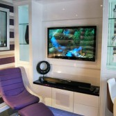 Bespoke living room furniture in white high gloss with wall mounted TV. Display cabniets to either side with LED lighting. Purple chair to the front.