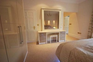Cream high gloss bedroom furniture with fitted wardrobes.