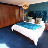 Fitted bedroom furniture: black walnut wardrobes, white bedsheets, turquoise throw and cushions.