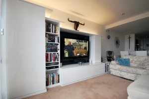 White high gloss bespoke living room furniture with book shelevs and flat screen TV.