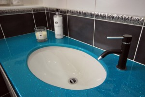 Bright blue bathroom top with white basin and black tap.