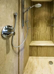 Natural granite look shower using Versital bathroom surfaces in 'Sandstone'. Versital shower tray, shower panels and shower seat.