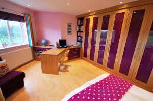 Purple hgih gloss and oak fitted furniture with desk area and book shelves.