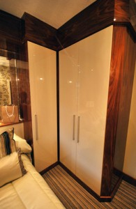 Bespoke fitted wardrobes in cream and black walnut high gloss.