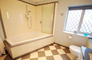 Large triangular shaped bath with shower panels in white sparkle with movable shower screen.