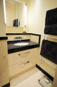 Custom white bathroom cabinet with black granite vanity top.