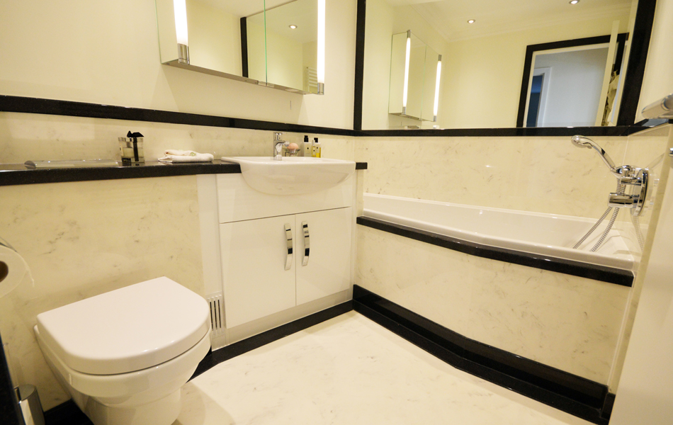 Black and white bathroom with shaped bath. Bespoke design made to order.