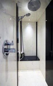 Large black and white shower with black seat and silver shower head.