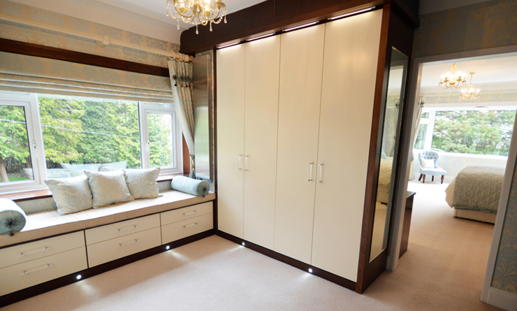 Dressing room wardrobe storage with light up doors painted in cream and matching sitting space with shelves