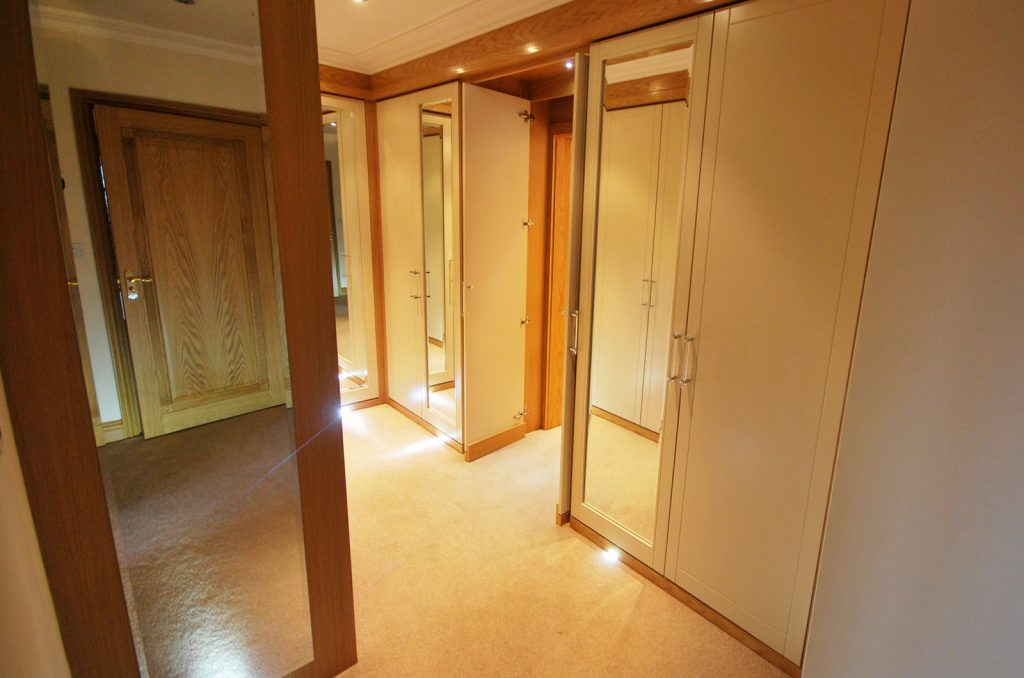Oak and cream fitted wardrobes create a warm and modern feel