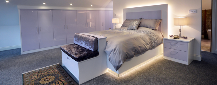 Fully fitted bedroom with light up bed in white and matching gloss white wardrobe full length of the wall