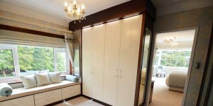 Dressing room wardrobe in black walnut and contrasting painted cream doors