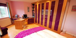 Kids bedroom furniture in high gloss purple and contrasting birch wood