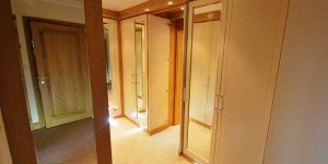 Walk in wardrobe with storage solutions and contrasting cream and oak panels