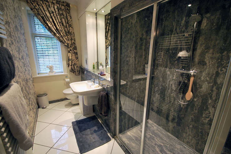 Granite style en-suite bathroom with large enclosed shower area and built in storage.