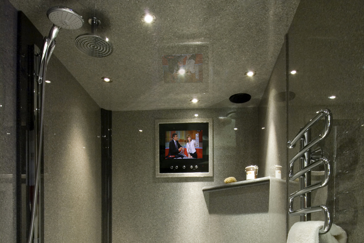 Wet room style grey shower area with walk in shower in granite finish with a wall mounted tv screen