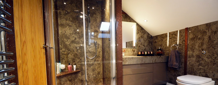 En-suite bathroom in cream and brown marble with metallic finish and sliding door shower enclosure