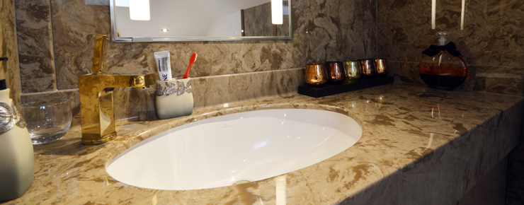 Vanity top wit a golden tap and under mounted basin compact cloakroom design