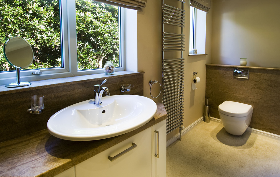Stylish bathroom design with splashback and vanity top in sandstone granite finish from versital with a geberit toilet and villeroy and boch sink